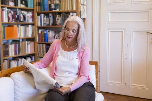 Mature woman sitting on couch at home reading newspaper - JUNF00668