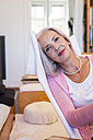 Mature woman sitting in armchair at home - JUNF00674