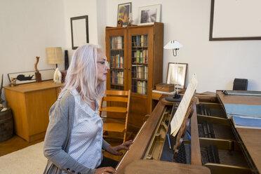 Woman playing piano at home - JUNF00677