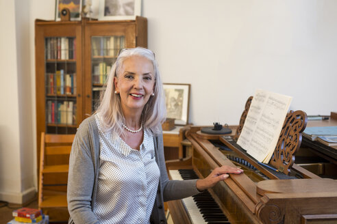 Portrait of smiling woman with piano at home - JUNF00680