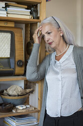 Pensive woman leaning against shelf at home - JUNF00686