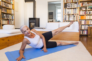 Woman exercising on gym mat in living room - JUNF00698