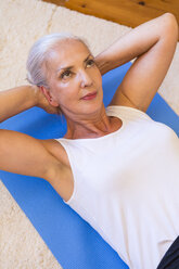 Portrait of woman exercising on gym mat in living room - JUNF00701