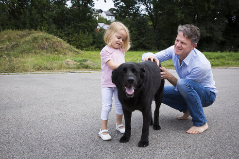 Father and daughter petting dog in garden - JTLF00119