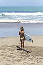 Indonesia, Bali, female surfer on the beach - KNTF00511