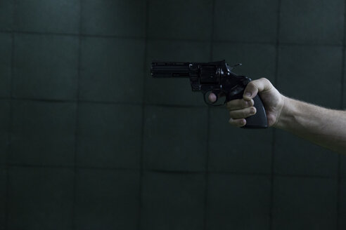 Hand of a man aiming with a revolver in an indoor shooting range - ABZF01275