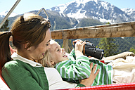 Happy mother and daughter relaxing on panorama terrace in the mountains - FSF00504