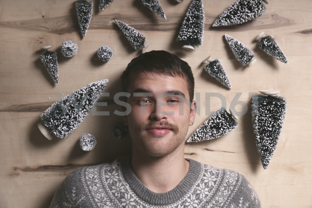 Young man lying on the floor surrounded by Christmas tree decoration - RTBF00396