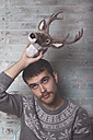 Young man holding artificial deer head - RTBF00405