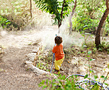 Back view of little boy playing with garden hose - VABF00778