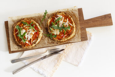 Two homemade glutenfree mini pizzas with cauliflower, pumpkin and rocket on wooden board - EVGF03075
