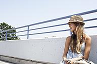 Teenage girl with headphones sitting on bridge - FSF00520