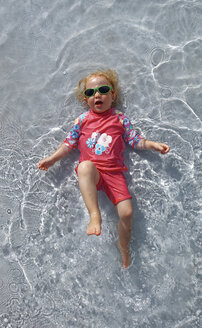 Clothed little girl with sunglasses  lying on back in water - LHF00505