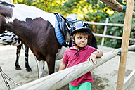 Little boy waiting to start riding lesson - VABF00798