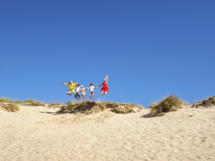 Family jumping from sand dune - LAF01764