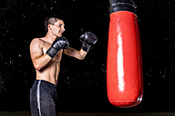 Boxer exercising with punch bag - STSF01101