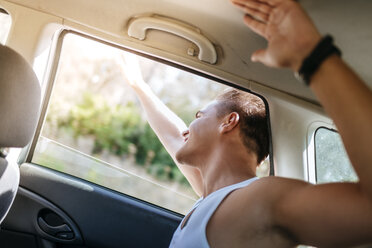 Happy young man leaning out of car window - KIJF00780