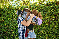 Couple kissing behind a skateboard - KIJF00795