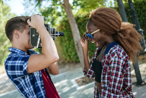 Young man filming his girlfriend with an old-fashioned camera - KIJF00807