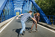 Happy young couple with inline skates and skateboard on a bridge - KIJF00816
