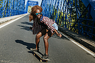 Young woman on skateboard on a bridge - KIJF00819