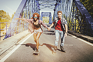 Young couple with inline skates and skateboard riding on a bridge - KIJF00822