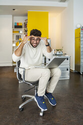 Young man with laptop in a modern office pulling funny faces - TCF05116