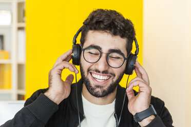 Portrait of laughing man with listening music with headphones - TCF05122
