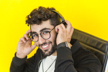Portrait of smiling man with glasses putting on headphones - TCF05125