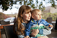 Mother and son sitting on chair looking around - MFF03370