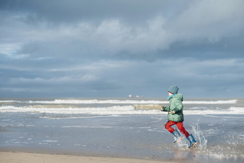 Denmark, Skagen, boy in winter clothes running on beach - MJF02014