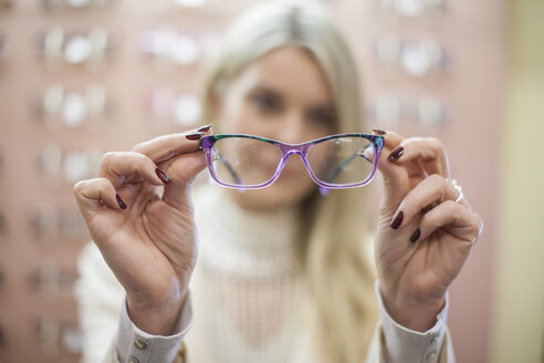 Blond woman selecting new glasses in opticians shop - ZEF10411