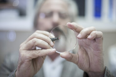 Optometrist looking through eydeglass lens - ZEF10417