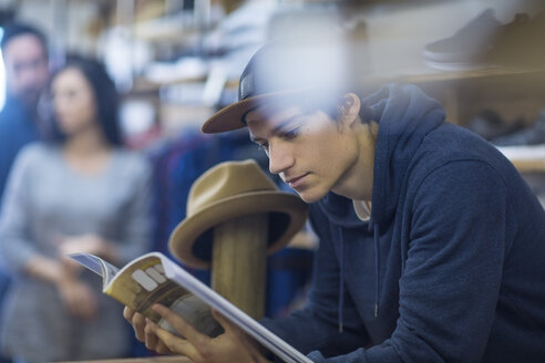 Young man in shop reading magazine - ZEF10462