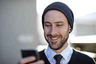 Young man wearing beanie holding cell phone - ZEF10474