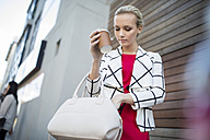Woman with takeaway coffee putting phone in handbag - ZEF10483