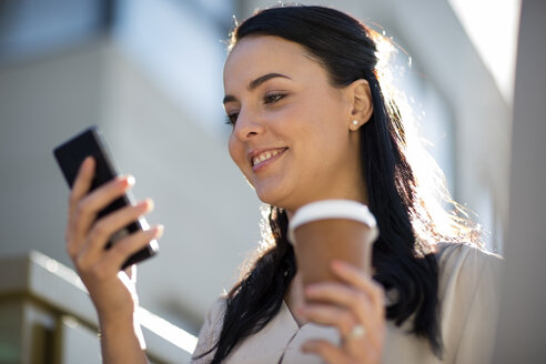 Smiling woman with takeaway coffee looking at cell phone - ZEF10495