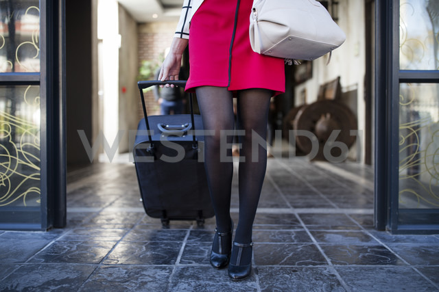 Legs of woman pulling suitcase out of building front door - ZEF10498