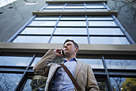 Buisnessman on cell phone outside building - ZEF10501