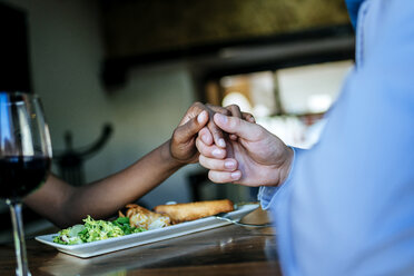 Close-up of a couple holding hands in restaurant - KIJF00845