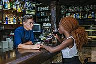 Waiter flirting with woman at a bar - KIJF00851