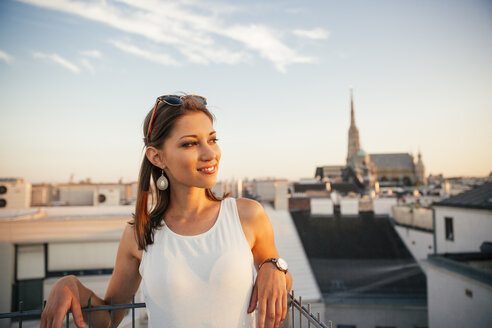 Austria, Vienna, portrait of smiling young woman on rooftop at sunset with Stephansdom in the background - AIF00374