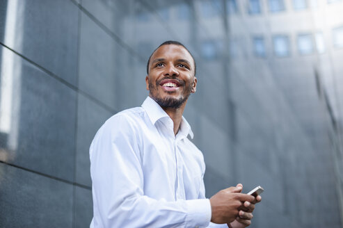 Portrait of content businessman with  cell phone - DIGF01318