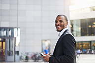 Portrait of smiling businessman with mini tablet - DIGF01339