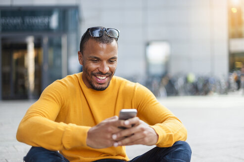 Smiling man wearing yellow pullover looking at cell phone - DIGF01345