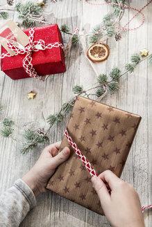 Hands of girl wrapping Christmas present - SARF02954