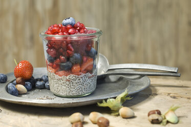 Glasses of chia pudding with different berries, pomegranate seeds and hazelnuts - ASF06025