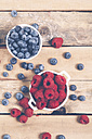 Bowls of raspberries and blueberries on wood - RTBF00415