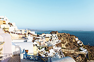 Greece, Santorini, Oia, view to the village at evening twilight with tourists waiting for sunset - GEMF01086