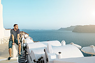 Greece, Santorini, Oia, man sitting on a wall enjoying sunset - GEMF01089